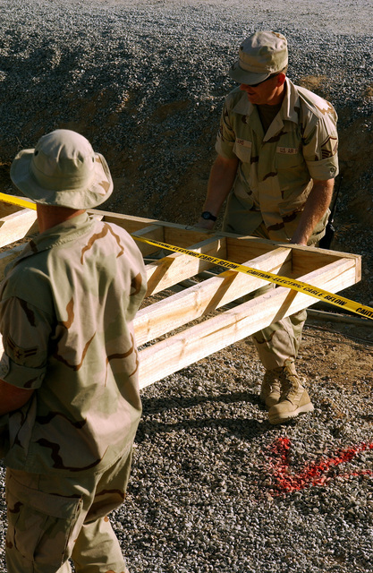 US Air Force (USAF) members, deployed to the 320th Expeditionary Civil Engineering Squadron (ECES), carry a ten-foot section of a support wall for a protective bunker at a forward-deployed location. The bunkers are part of the continuous build up at forward-deployed locations supporting Operation ENDURING FREEDOM