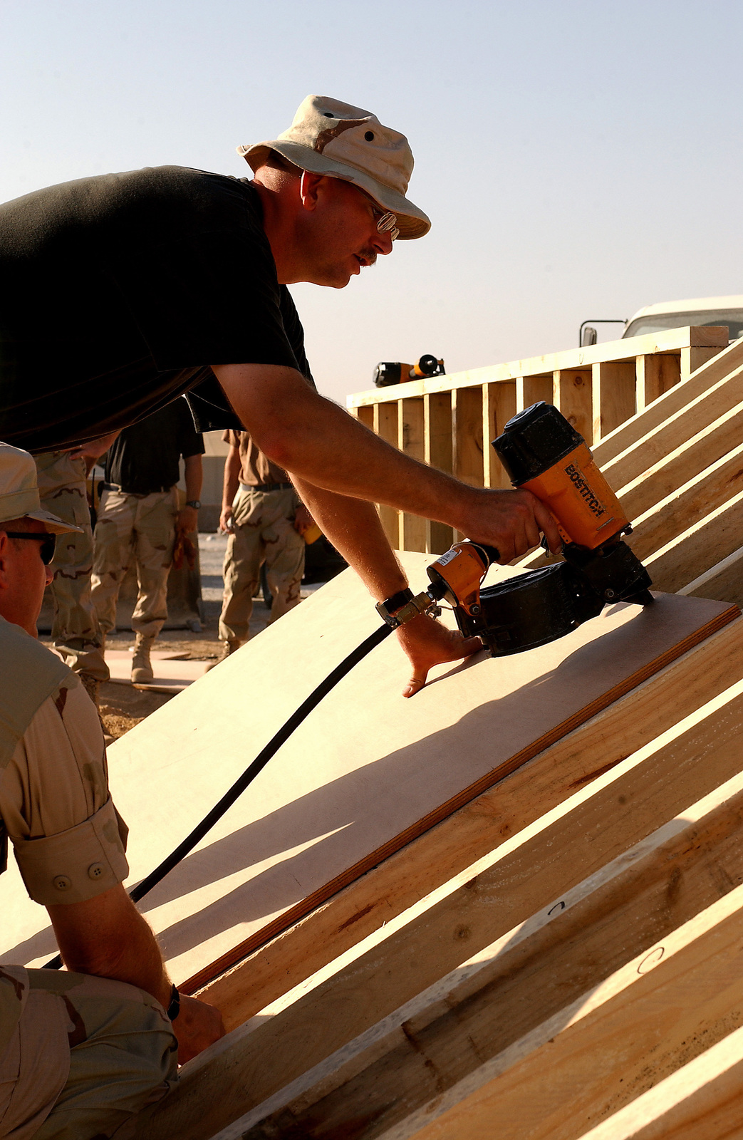US Air Force (USAF) STAFF Sergeant (SSGT) Virgil Deaton, Structural Craftsman, 320th Expeditionary Civil Engineering Squadron (ECES), uses a nail gun to attach a board onto a support wall for a bunker at a forward deployed location. The bunkers are part of the continuous build up at forward-deployed locations supporting Operation ENDURING FREEDOM