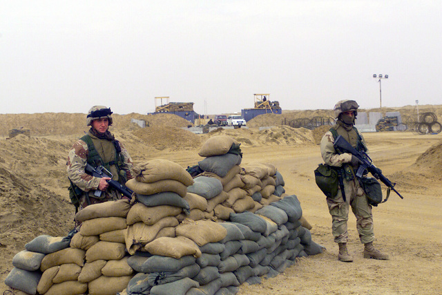 US Marine Corps (USMC) Corporal (CPL) Jeffery Pioszak (left) and USMC Private First Class (PFC) Khristopher Williams, armed with5.56mm M16A2 rifles, man a bunkered security position a the entrance to the ammunition re-supply at Camp Coyote in Northern Kuwait during Operation ENDURING FREEDOM
