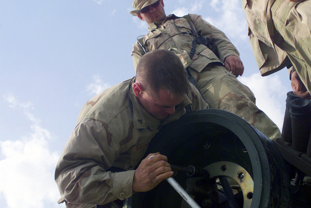US Marine Corps (USMC) Lance Corporal (LCPL) Christopher Brumlow, Alpha/Company, 2nd Tank Battalion, performs maintenance on a spare tank wheel at Camp Coyote in Northern Kuwait during Operation ENDURING FREEDOM