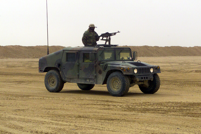 US Marine Corps (USMC) Marines provide security at an ammunition distribution point at Camp Coyote in Northern Kuwait with a High-Mobility Multi Purpose Vehicle (HMMWV) with a 7.62mm M240G machine gun mounted on top, during Operation ENDURING FREEDOM