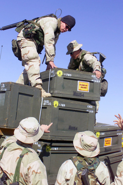 US Marine Corps (USMC) personnel assigned to Headquarters, 5th Marine Regiment, 1ST Marine Division, offload supplies at Camp Coyote in Northern Kuwait during Operation ENDURING FREEDOM