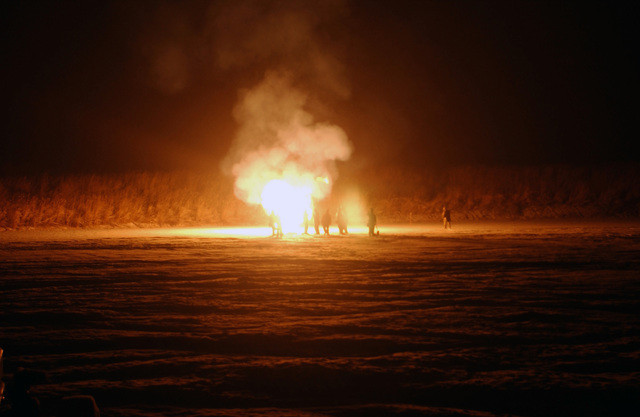 US Marine Corps (USMC) personnel of Sierra Battery, 5th Battalion, 10th Marine Regiment stand close to a powder burn in order to stay warm before going to sleep for the night. A powder burn gets rid of gunpowder that was not used during the day on the East Fuji Maneuver Area (FMA), Japan (JPN)