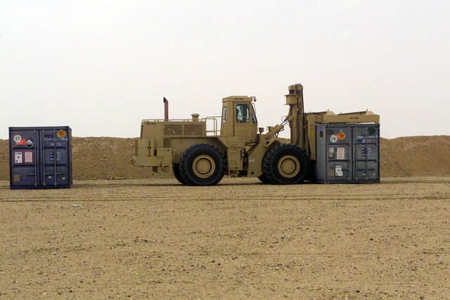 US Marine Corps (USMC) personnel use a Rough Terrain Container Handler (RTCH) to position a International Standards Organization (ISO) container inside the ammunition re-supply point, Camp Coyote, Kuwait, during Operation ENDURING FREEDOM