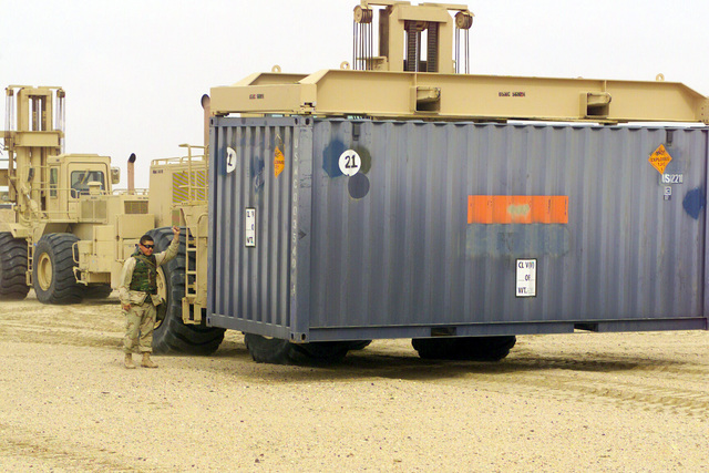 US Marine Corps (USMC) personnel use a Rough Terrain Container Handlers (RTCH) to position a International Standards Organization (ISO) container inside the ammunition re-supply point, Camp Coyote, Kuwait, during Operation ENDURING FREEDOM