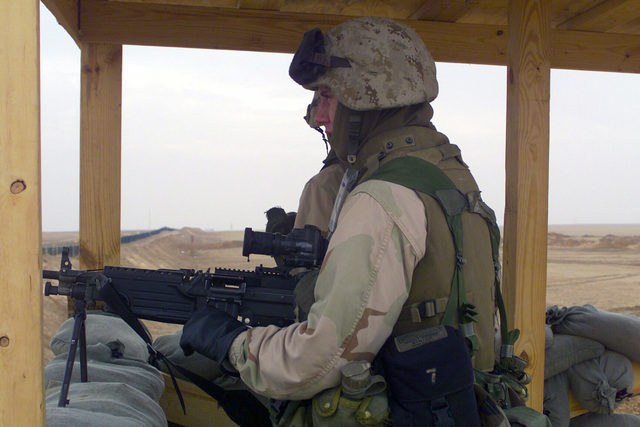 US Marine Corps (USMC) Private First Class (PFC) Marcus Ward, mans a 5.56mm M249 Squad Automatic Weapon (SAW) as he stands watch in a tower overlooking the ammunition re-supply point, Camp Coyote, Kuwait, during Operation ENDURING FREEDOM