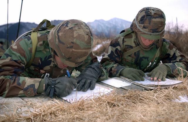 US Marine Corps (USMC) Second Lieutenant (2LT) Caleb Hyatt, a Forward Observer, and Lance Corporal (LCPL) Slicker, a Scout Observer, both with Sierra Battery, 5th Battalion, 10th Marine Regiment, plot safety box grids on a map to mark the gun lines designated area of fire on the East Fuji Maneuver Area (FMA), Japan (JPN)