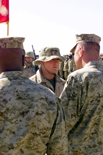 US Marines from Task Force Five at Camp Coyote, a Forward Area Supply Point (FASP), watch as General (GEN) Michael W. Hagee, Commandant of the Marine Corps, promotes Lance Corporal (LCPL) Swain during Operation ENDURING FREEDOM