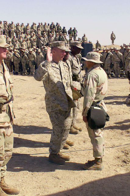 US Marines from Task Force Five at Camp Coyote, a Forward Area Supply Point (FASP), watch as General (GEN) Michael W. Hagee, Commandant of the Marine Corps, re-enlists Sergeant (SGT) Hernandez, during Operation ENDURING FREEDOM