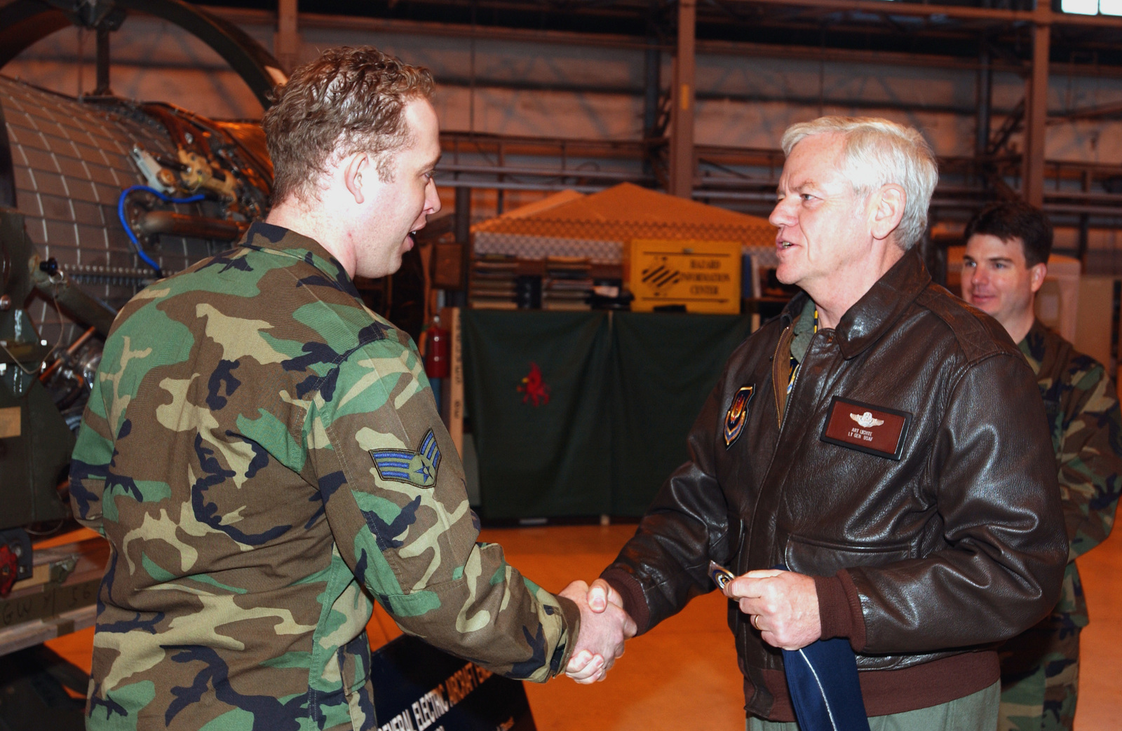 After presenting a quick rundown of the duties performed by the Propulsion Flight, US Air Force (USAF) SENIOR AIRMAN (SRA) Joshua Vines, Support Team Leader, 31st Maintenance Squadron (MXS), Aviano Air Base (AB), Italy, is presented a USAFE coin by USAF Lieutenant General (LGEN) Arthur J. Lichte, Vice-Commander, United States Air Forces in Europe (USAFE). The General is at Aviano AB for an orientation briefing