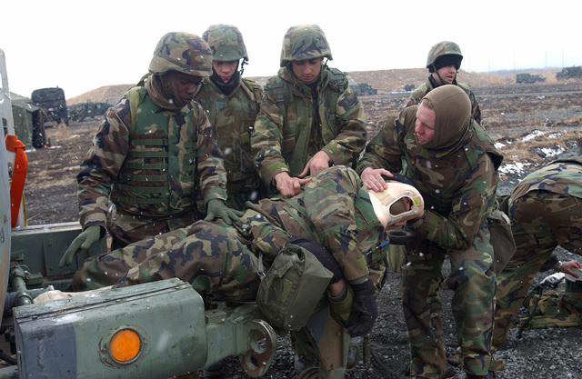 During a casualty drill (left to right) US Navy (USN) Hospital Corpsman 3 (HM3) Theodore Dowie, Religious Programs SPECIALIST SEAMAN (RPSN) Andrew Ruth, HM3 Jeoffrey Kennedy and HM3 Derek Haberzettl, all assigned to Sierra Battery, 5th Battalion, 10th Marine Regiment, assist acting victim US Marine Corps (USMC) Lance Corporal (LCPL) Robbert Willis, also with Sierra Btry, 5/10. The Corpsmen participated in this training at the East Fuji Maneuver Area (FMA), Japan (JPN)