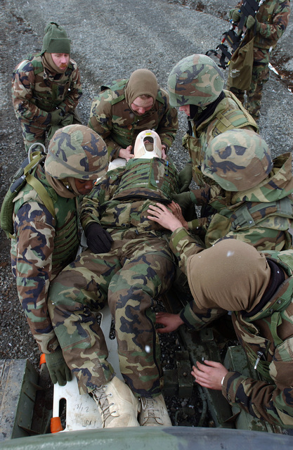 During a casualty drill US Navy (USN) Hospital Corpsman 3 (HM3) Theodore Dowie, Religious Programs SPECIALIST SEAMAN (RPSN) Andrew Ruth, HM3 Jeoffrey Kennedy and HM3 Derek Haberzettl, all assigned to Sierra Battery, 5th Battalion, 10th Marine Regiment, assist acting victim US Marine Corps (USMC) Lance Corporal (LCPL) Robbert Willis, also with Sierra Btry, 5/10. The Corpsmen participated in this training at the East Fuji Maneuver Area (FMA), Japan (JPN)