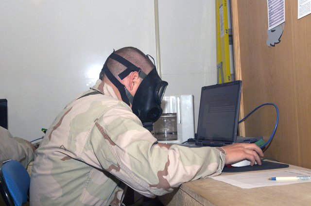 Sergeant (SGT) Nicholas S. Hizer of Marine Wing Support Squadron (MWSS) 373rd Combat Camera team works on his laptop during the gas mask familiarization exercise at Ahmed Al Jaber Air Base, Kuwait, in support of Operation ENDURING FREEDOM