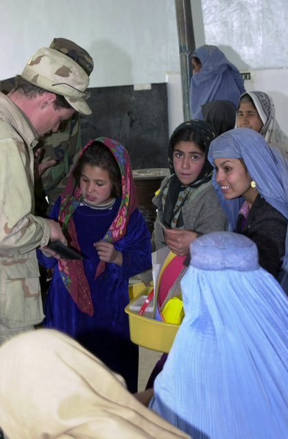 SPECIALIST Fourth Class (SPC) Brian Roberts of the 310th Civil Affairs Battalion (CAB) speaks with Afghan women and children during a Medical Civil Action Program (MEDCAP) in the village of Pol-e Charkhi, in support of Operation ENDURING FREEDOM