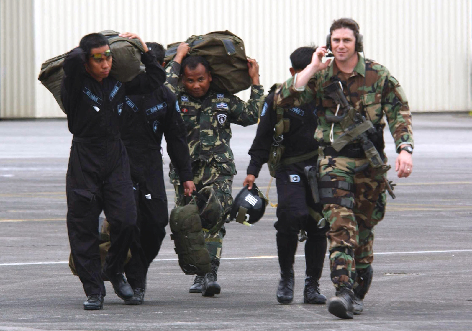 US Air Force (USAF) STAFF Sergeant (SSGT) Michael Paulson (right), Combat Controller, 320th Special Tactics Squadron (STS), Kadena Air Base (AB), Japan, together with members of the Philippine Air Force (PAF) heads toward their aircraft for a joint parachute training during exercise BALANCE PISTON 03-5. The joint exercise is designed to improve the interoperability and tactical proficiency of the armed forces of the US and Philippines