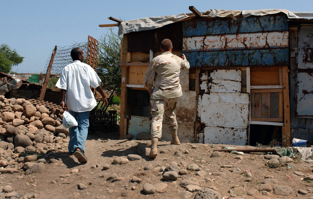 US Army (USA) Sergeant (SGT) Joseph Kilmer, 354th Civil Affairs Brigade (CAB), US Army Reserve, Riverdale, Maryland (MD), compliments Omar Farah Dabar, CHIEF of the village of Sud Homboli, Djibouti, on the recent addition to his home. Omar Farah Dabar built the 10-foot addition to his home using wood donated by the US military members assigned to Camp Lemonier, Djibouti, Africa, during Operation ENDURING FREEDOM. Civil Affairs (CA) acts as a liaison between the local community and Camp Lemonier, often acting as the direct representative for the base commander