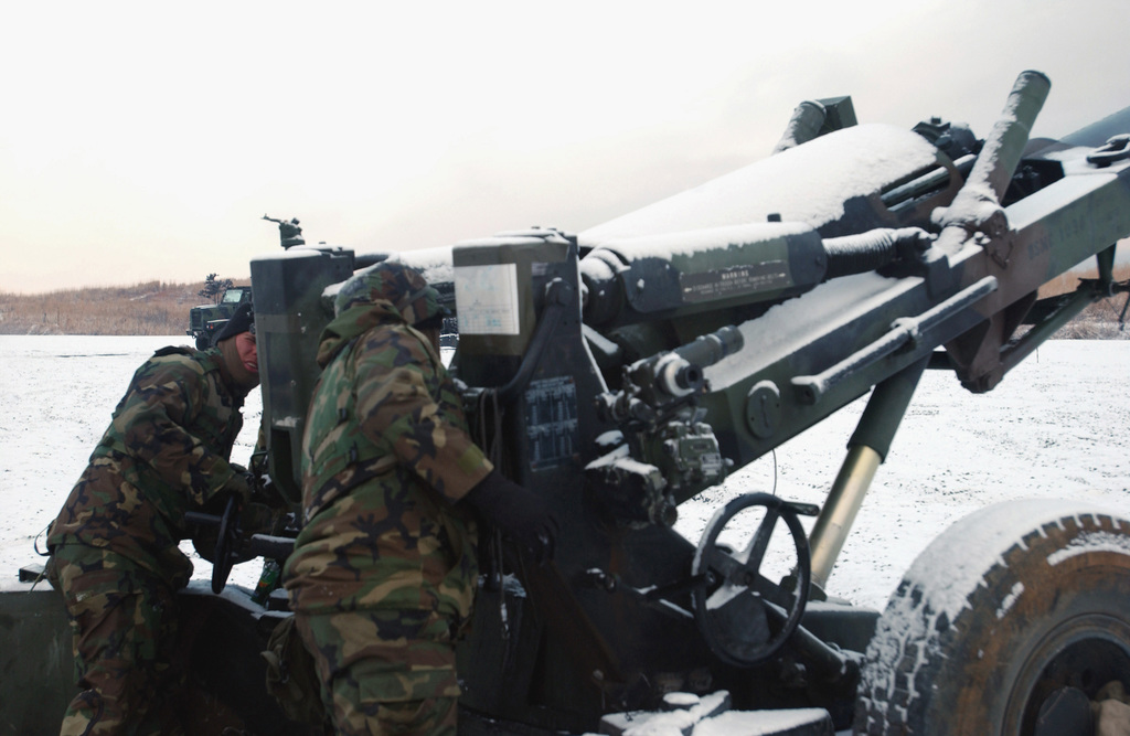 US Marine Corps (USMC) Marines assigned to S/Battery, 5th Battalion, 10th Marine Regiment, adjust the position of the M198 155mm, Medium Range Howitzer during a live fire drill on the range at the East Fuji Maneuver Area, Okinawa, Japan