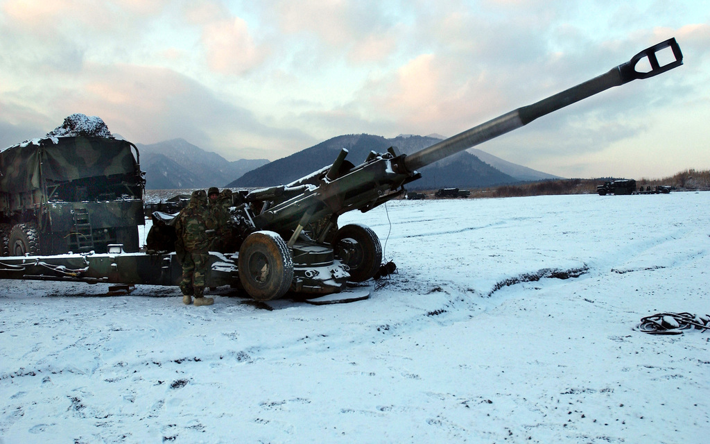 US Marine Corps (USMC) Marines assigned to S/Battery, 5th Battalion, 10th Marine Regiment, fire their M198 155mm, Medium Range Howitzer during a live fire drill on the snow covered range at the East Fuji Maneuver Area, Okinawa, Japan