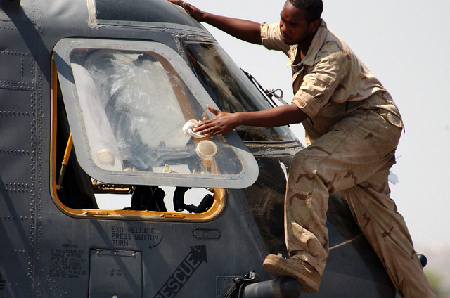 A US Air Force (USAF) maintenance member cleans the side windows of a USAF MH-53M Pave Low IV on the flightline of Camp Lemonier, Djibouti, during Operation ENDURING FREEDOM