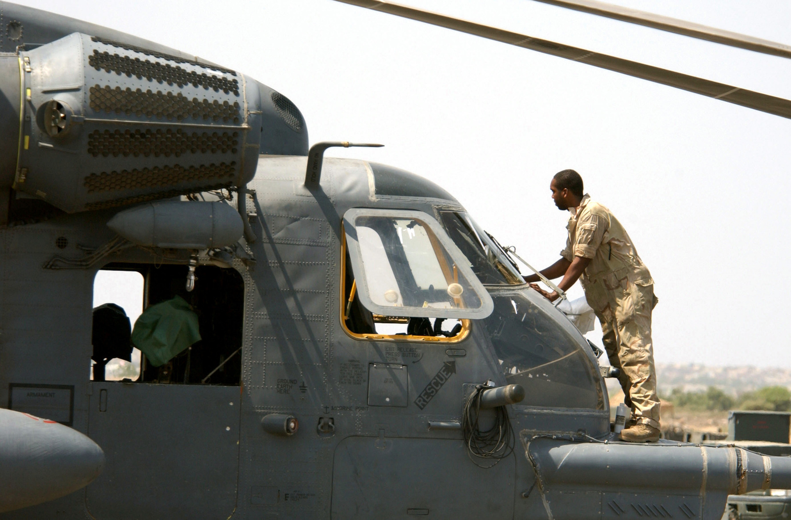 A US Air Force (USAF) maintenance member cleans the windshield of a USAF MH-53M Pave Low IV on the flightline of Camp Lemonier, Djibouti, during Operation ENDURING FREEDOM