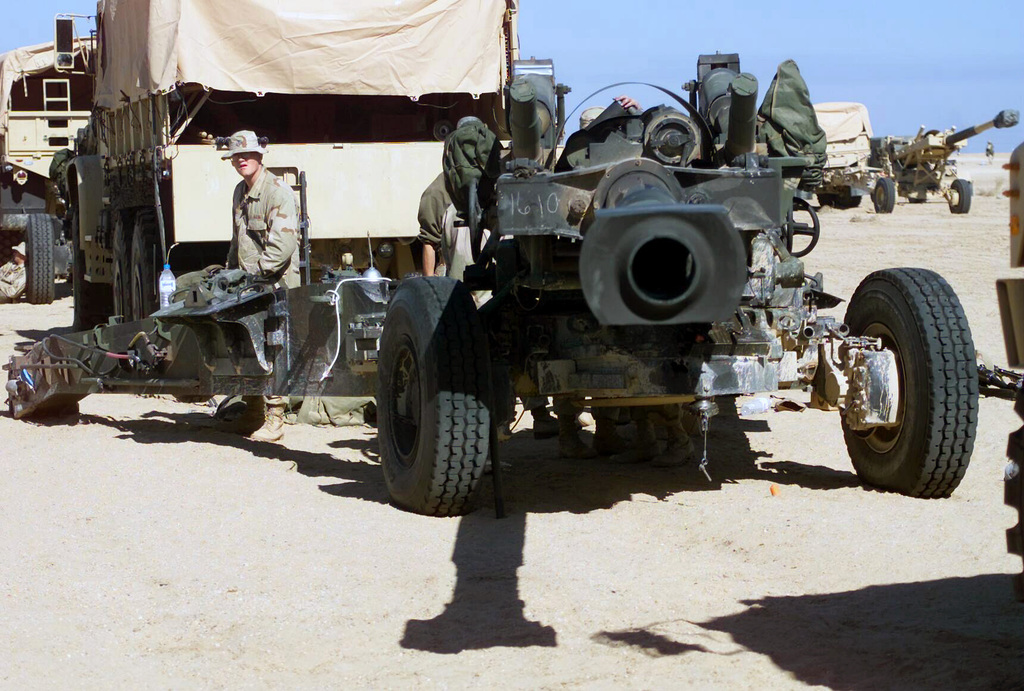 A US Marine Corps (USMC) 155mm Howitzer M198 is serviced by USMC personnel assigned to T/Battery, 5/11 7th Marines, at Camp Coyote, Kuwait, during Operation ENDURING FREEDOM