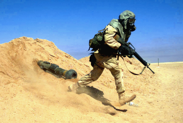 Taking off after his partner fired and discarded a Javelin Missile Training tube, US Marine Corps (USMC) Corporal (CPL) Kelly Smith, 7th Marines 3rd Battalion, 4th Marines (3/4) Weapons Company, participates in Nuclear Biological Chemical (NBC) training. CPL Smith is wearing his M40A1 Chemical-Biological Mask and hood, full gear and 5.56 mm M16A2 rifle, for the training during Operation ENDURING FREEDOM at Camp Coyote, Kuwait
