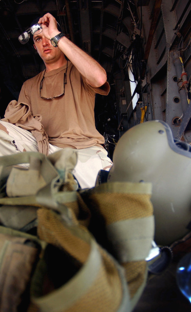 US Air Force (USAF) STAFF Sergeant (SSGT) Glenn Fleming, Aerial GUNNER, Air Force Special Operations (AFSO) Detachment, Camp Lemonier, Djibouti, cleans his glasses onboard a USAF MH-53M Pave Low IV prior to conducting dust-out training during Operation ENDURING FREEDOM