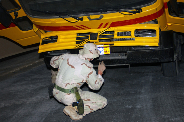 US Air Force (USAF) STAFF Sergeant (SSGT) Thaddeus, 384th Expeditionary Security Forces Squadron (ESFS), searches a truck at the new search pit before clearing it to go on base at forward-deployed location