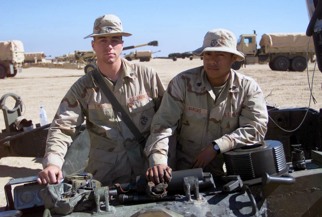 US Marine Corps (USMC) Corporal (CPL) Taylor (left) and Lance Corporal (LCPL) Vargas, both assigned to T/Battery, 5/11 7th Marines, service their 155mm Howitzer M198, at Camp Coyote, Kuwait, during Operation ENDURING FREEDOM