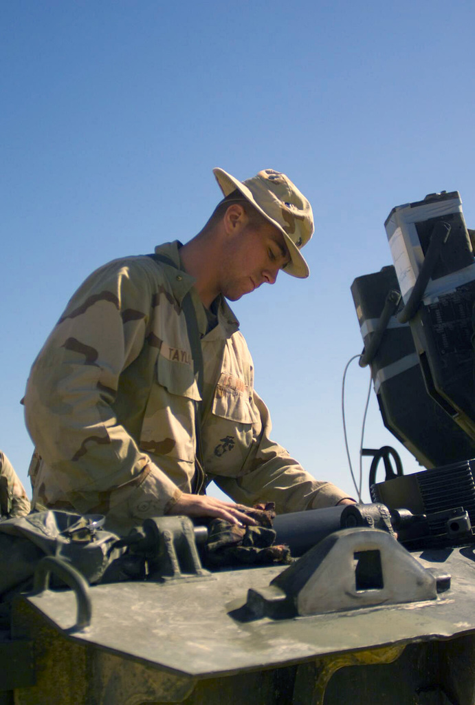 US Marine Corps (USMC) Corporal (CPL) Taylor, T/Battery, 5/11 7th Marines, performs routine service on a 155mm Howitzer M198, at Camp Coyote, Kuwait, during Operation ENDURING FREEDOM