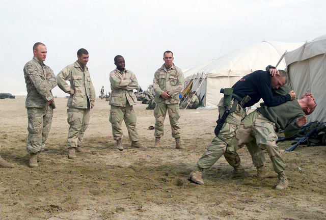 US Marine Corps (USMC) GUNNERY Sergeant (GYSGT) Brian Davis and USMC Corporal (CPL) Aaron Oakes, 7th Marines 3/4 Headquarters/Support Company demonstrates proper Marine Corps Martial Arts (MCMAP) techniques at Camp Coyote, Kuwait during, Operation ENDURING FREEDOM