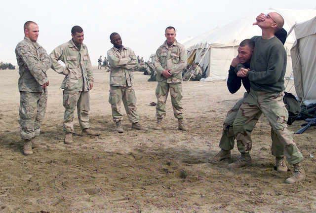 US Marine Corps (USMC) GUNNERY Sergeant (GYSGT) Brian Davis and USMC Corporal (CPL) Aaron Oakes, 7th Marines 3/4 Headquarters/Support Company demonstrates proper Marine Corps Martial Arts (MCMAP) techniques at Camp Coyote, Kuwait, during Operation ENDURING FREEDOM