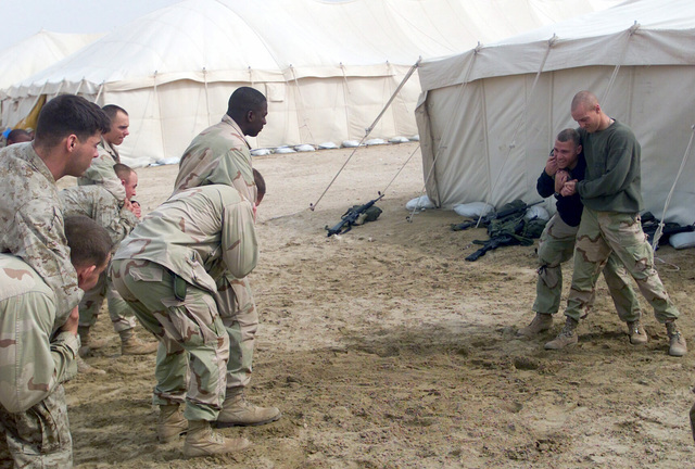 US Marine Corps (USMC) GUNNERY Sergeant (GYSGT) Brian Davis and USMC Corporal (CPL) Aaron Oakes (right), demonstrates proper Marine Corps Martial Arts (MCMAP) techniques to USMC personnel assigned to 7th Marines 3/4 Headquarters/Support Company at Camp Coyote, Kuwait, during Operation ENDURING FREEDOM