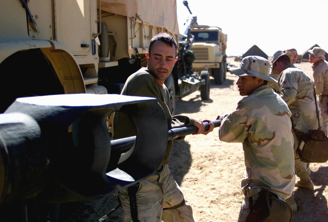 US Marine Corps (USMC) Marines from Tango battery 5th Battalion, 11th Marines (5/11) 7th Marines, service the barrel of their M198 155mm Howitzer during Operation ENDURING FREEDOM at Camp Coyote, Kuwait