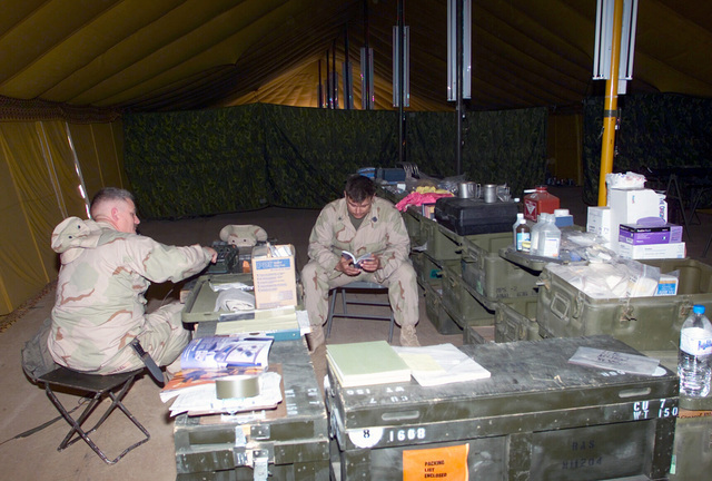 US Navy (USN) Hospital Corpsman, PETTY Officer Third Class (HM3) Jason Delon (center), assigned to 7th Marines 3/4 Headquarters/Support Company, helps to checks medical supplies inside the Medical Tent at Camp Coyote, Kuwait, during Operation ENDURING FREEDOM
