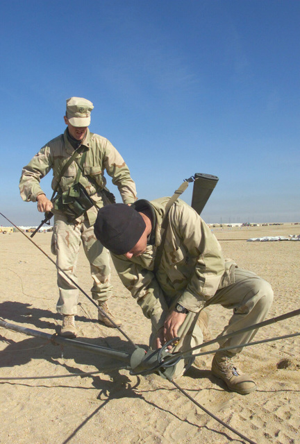 A Marine from Regimental Combat Team 7 (RCT-7) (7th Marine Regiment (Rein)), Twentynine Palms, California, attaches an HF Band Discone antenna for communications at Camp Coyote, Kuwait, onto a mast, during Operation ENDURING FREEDOM, as another Marine checks the guidelines. The Marines carry their 5.56mm M16A2 always at hand