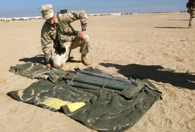 A Marine with the Regimental Combat Team 7 (RCT-7) (7th Marine Regiment (Rein)), Twentynine Palms, California, prepares to unpack an antenna mast from its field pack at Camp Coyote, Kuwait during Operation ENDURING FREEDOM. The Marine carries his 5.56mm M16A2 always at hand