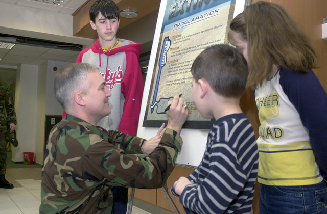 At the Ramstein Air Base (AB) Dental Clinic, US Air Force (USAF) Brigadier General (BGEN) Erwin F. Lessel lll, Commander, 86th Airlift Wing (AW), receives help signing a proclamation promoting Children's Dental Health month from Joshua, Zachary and Nicole Barclay, children of Captain (CAPT) James and Brenda Barclay