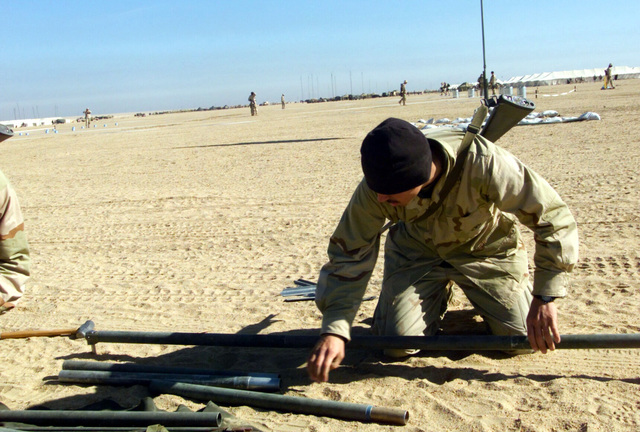 Marines from Regimental Combat Team 7 (RCT-7) (7th Marine Regiment (Rein)), Twentynine Palms, California, assemble an antenna mast at Camp Coyote, Kuwait during Operation ENDURING FREEDOM. The Marines carry their 5.56mm M16A2 always at hand