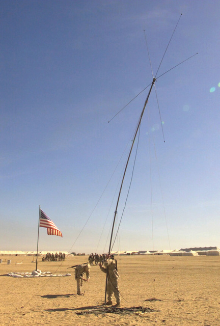Marines from Regimental Combat Team 7 (RCT-7) (7th Marine Regiment (Rein)), Twentynine Palms, California, raise an HF Band Discone antenna for communications at Camp Coyote, Kuwait, during Operation ENDURING FREEDOM