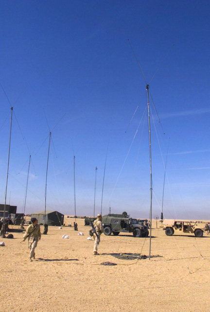 Marines from Regimental Combat Team 7 (RCT-7) (7th Marine Regiment (Rein)), Twentynine Palms, California, raise one more HF Band Discone antenna as part of Combat Operations Center (COC), 1ST Battalion 7th Marines Regiment, Bravo Company, Twentynine Palms, California, antenna farm at Camp Coyote, Kuwait during Operation ENDURING FREEDOM