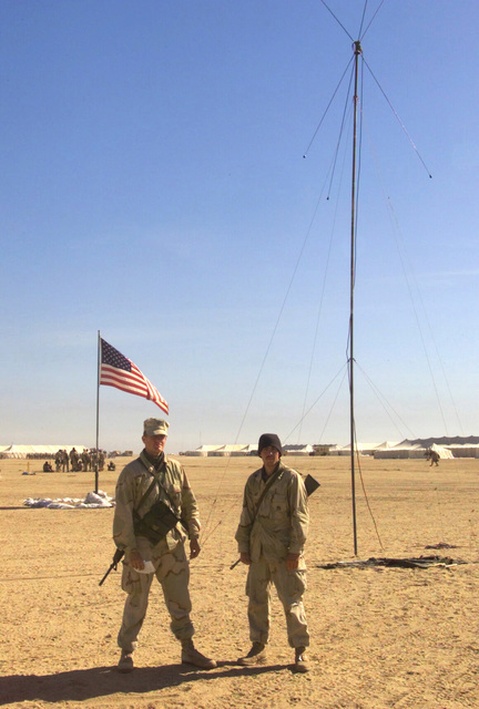 Marines from Regimental Combat Team 7 (RCT-7) (7th Marine Regiment (Rein)), Twentynine Palms, California, pose for a shot after raising one more HF Band Discone antenna as part of Combat Operations Center (COC), 1ST Battalion 7th Marines Regiment, Bravo Company, Twentynine Palms, California, antenna farm at Camp Coyote, Kuwait during Operation ENDURING FREEDOM. The Marine carrys his 5.56mm M16A2 always at hand