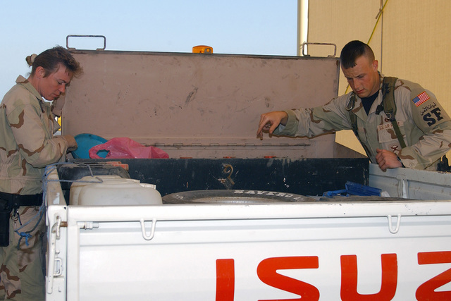 US Air Force (USAF) STAFF Sergeant (SSGT) Laura Palmer (left) and USAF AIRMAN First Class (A1C) Joshua Lyons, 384th Expeditionary Security Forces Squadron (ESFS), search all vehicles for contraband and weapons in the search pit at the 384th Air Expeditionary Wing (AEW) forward deployed location