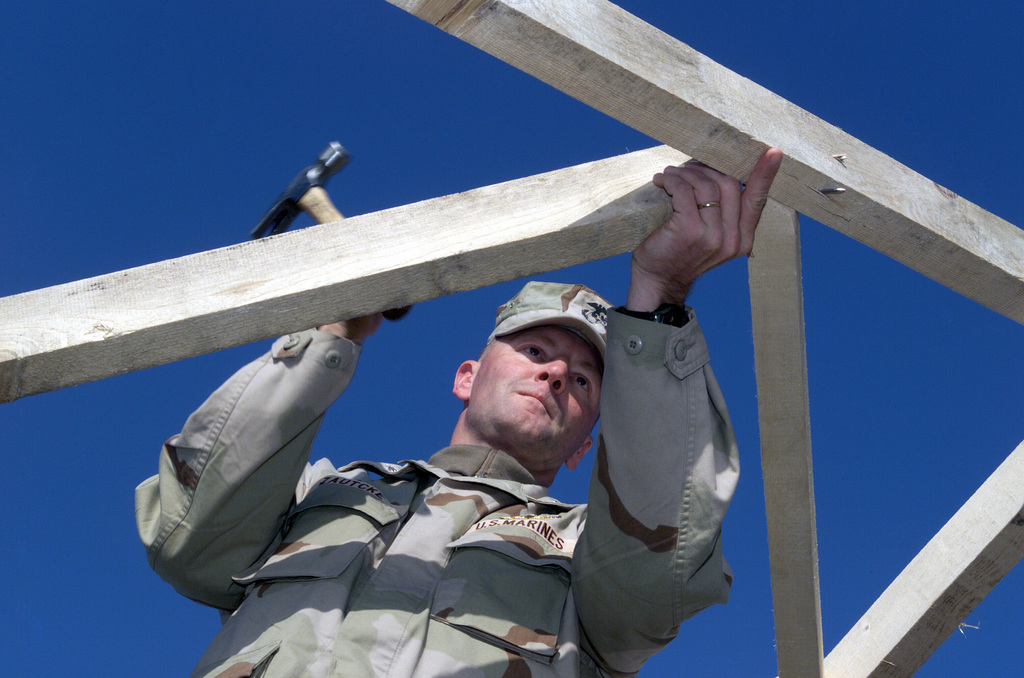 US Marine (USMC) Wing Support Squadron (MWSS) 373rd Commanding Officer (CO), Lieutenant Colonel (LCOL) Donald W. Zautcke ceremoniously adds the final nails into the supporting beam of the hardback tent living quarters, at Camp Sledd on Ahmed Al Jaber Air Base, Kuwait, in support of Operation ENDURING FREEDOM