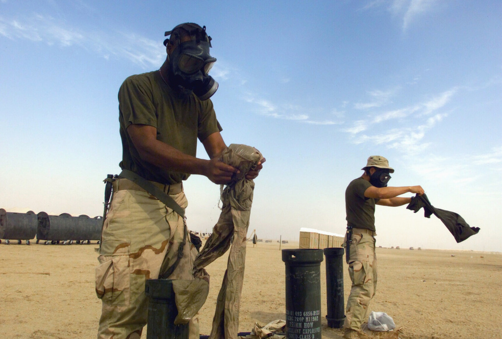 Wearing their M40A1 Chemical-Biological Masks, US Marine Corps (USMC) Lance Corporal (LCPL) Craig Aubert (right) and LCPL Juan Pablo Samayoa, 7th Marines 5th Battalion, 11th Marines (5/11) Romeo Company use empty 155mm Howitzer shell casings to do their laundry during Operation ENDURING FREEDOM at Camp Coyote, Kuwait