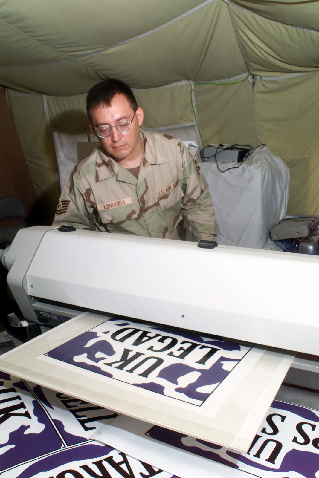 US Air Force (USAF) Technical Sergeant (TSGT) Christopher Longoria, Graphics Craftsman, 379th Expeditionary Communication Squadron (ECS), Al Udeid AB Qatar, laminates a graphics poster at Al Udeid AB Qatar, during Operation ENDURING FREEDOM