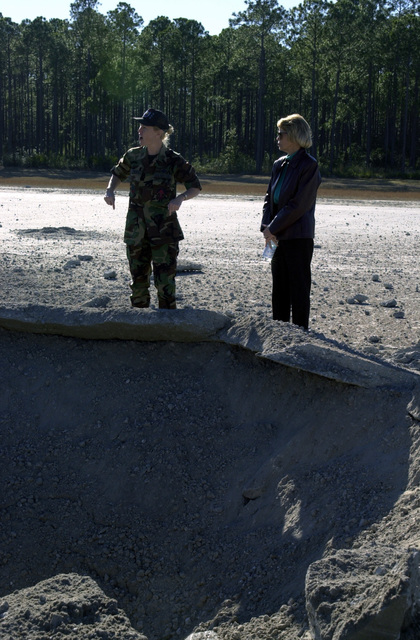 US Marine Corps (USMC) Major (MAJ) Jani McCreary, left, with Detachment 1, 823rd Red Horse Squadron (RHS), Commander, shows Karen Hanes, a Chairperson of the Military Affairs Committee what a runway crater at the Silver Flag exercise site looks like