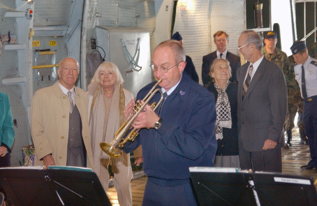 "Inside the cargo compartment of a US Air Force (USAF) C-5A Galaxy aircraft, USAF Technical Sergeant (TSGT) Jim Masters, Non-Commissioned Officer in Charge (NCOIC) of the Travis Brass, plays the tune ""Volare"" on the trumpet, as Mr. & Mrs. Robert Mondavi (left), Owners of the Robert Mondavi Winery, and Mrs. Janine Graber with Mr. Raymond C. Carrington, looking on. The distinguished visitors were give a tour of the aircraft by US Air Force (USAF) Brigadier General (BGEN) Brad Baker, (not shown) Commander, 60th Air Mobility Wing (AMW), at Travis Air Force Base (AFB), California (CA)"
