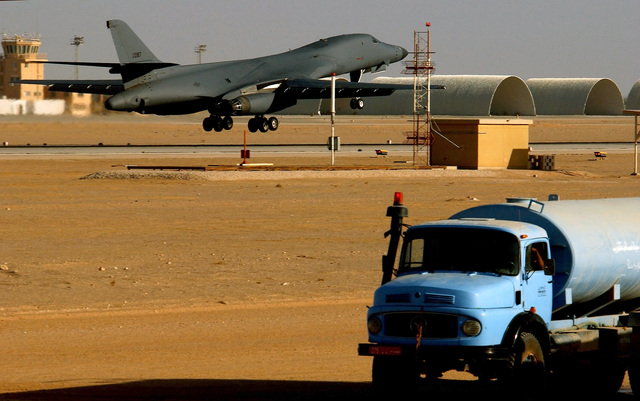 A US Air Force (USAF) B-1B Lancer aircraft lands at an undisclosed forward deployed location during Operation ENDURING FREEDOM. A water tanker being used during a taxiway and support ramp construction project is visible in the foreground