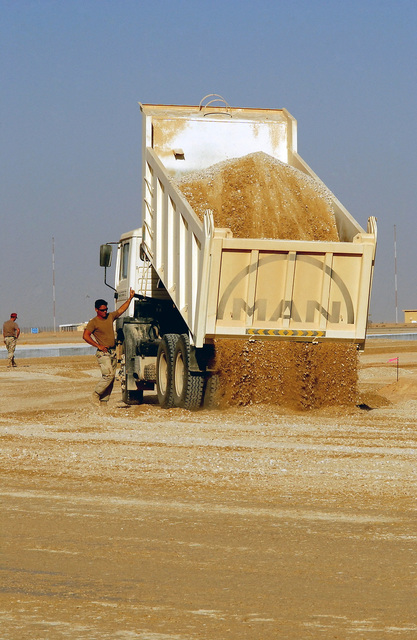 A US Air Force (USAF) Heavy Equipment Operator assigned to the 823rd Red Horse Squadron (RHS), drops a load of gravel from a (6x6) 20-ton dump truck, during a taxiway and support ramp construction project at a forward deployed location during Operation ENDURING FREEDOM